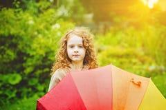 Kleines Mädchen mit Regenbogenregenschirm, unter Sonnenschein Lizenzfreie Stockfotos