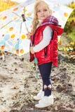 Kleines Mädchen mit Regenschirm in der roten Weste im Freien Lizenzfreie Stockbilder