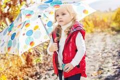 Kleines Mädchen mit Regenschirm in der roten Weste im Freien Lizenzfreies Stockfoto
