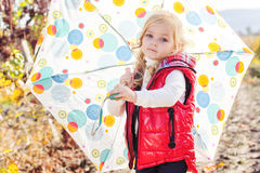 Kleines Mädchen mit Regenschirm in der roten Weste im Freien Stockbilder