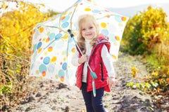 Kleines Mädchen mit Regenschirm in der roten Weste im Freien Lizenzfreies Stockbild