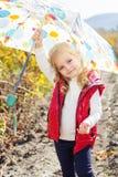 Kleines Mädchen mit Regenschirm in der roten Weste im Freien Stockfotos
