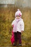 Kleines Mädchen mit rosa Regenschirm im Herbstpark Stockfoto