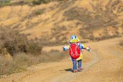 Kleines Mädchen mit Rucksackreise auf der Straße Lizenzfreie Stockbilder