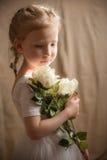 Kleines Mädchen mit sahnigen Rosen Lizenzfreie Stockfotografie