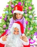 Kleines Mädchen mit Santa Claus Stockfoto