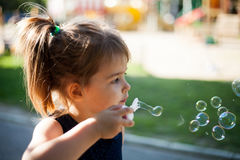 Kleines Mädchen mit Schlagblasen des langen Haares draußen lizenzfreies stockbild