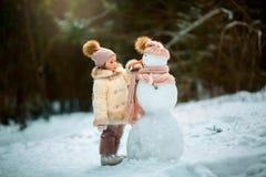 Kleines Mädchen mit Schneemann Lizenzfreies Stockbild