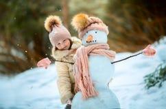 Kleines Mädchen mit Schneemann Lizenzfreie Stockfotos