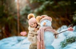 Kleines Mädchen mit Schneemann Stockfotografie