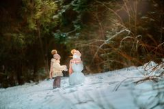 Kleines Mädchen mit Schneemann Stockfotos