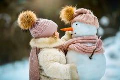 Kleines Mädchen mit Schneemann Lizenzfreie Stockfotografie