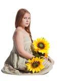Kleines Mädchen mit Sommerhut und -sonnenblumen Lizenzfreie Stockfotos