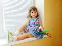 Kleines Mädchen mit Spielzeugblumenstrauß Stockfotos