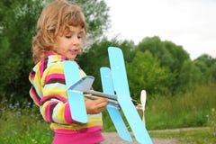 Kleines Mädchen mit Spielzeugflugzeug in den Händen im Freien Stockfotos