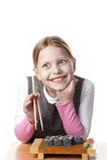 Kleines Mädchen mit Sushi Stockfotos