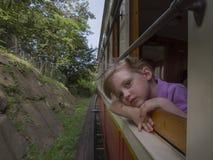 Kleines Mädchen mit träumerischen Augen reist im Zug Stockfoto