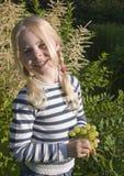 Kleines Mädchen mit Traube im Garten Stockbild