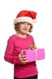 Kleines Mädchen mit Weihnachtsgeschenk und Sankt-Hut Stockbild