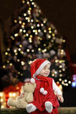 Kleines Mädchen mit Weihnachtshut und Teddybär betreffen Schwarzes Lizenzfreies Stockbild