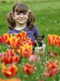 Kleines Mädchen mit Welpen im Blumengarten stockbild