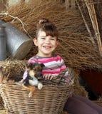 Kleines Mädchen mit Welpen im Korb lizenzfreies stockbild