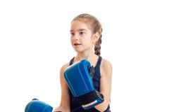 Kleines Mädchen mit Zöpfen in den Boxhandschuhen blickt in Richtung Stockbild