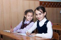 Kleines Mädchen mit Zöpfen lächelnd in der Klasse Stockfotografie