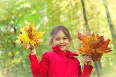 Kleines Mädchen mit zwei Blumensträußen Stockbild