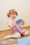 Kleines Mädchen montiert Puzzlespiele in einem Raum Stockfoto