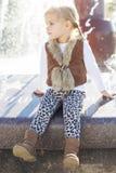 Kleines Mädchen nahe Brunnen, Herbstzeit Stockfoto