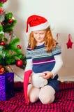 Kleines Mädchen nahe dem Weihnachtsbaum mit Geschenken Lizenzfreies Stockfoto