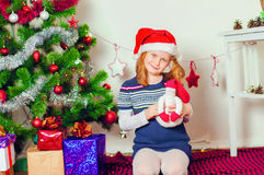 Kleines Mädchen nahe dem Weihnachtsbaum mit Geschenken Lizenzfreies Stockbild