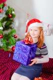 Kleines Mädchen nahe dem Weihnachtsbaum mit Geschenken Stockfoto
