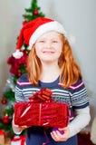 Kleines Mädchen nahe dem Weihnachtsbaum mit Geschenken Stockbilder