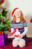 Kleines Mädchen nahe dem Weihnachtsbaum mit Geschenken Stockbild