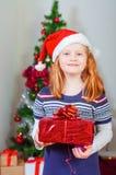 Kleines Mädchen nahe dem Weihnachtsbaum mit Geschenken Stockfotos