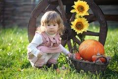 Kleines Mädchen nahe großem Kürbis und Sonnenblume Stockfotografie