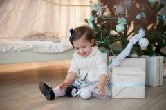 Kleines Mädchen nahe Weihnachtsbaum mit Geschenken freut sich Feiertag, neues Jahr, Dekorationen, Geschenk, Kasten, Feiertag, Leb Lizenzfreie Stockfotografie