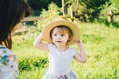 Kleines Mädchen nimmt Mutter ` s Hut Stockfotografie