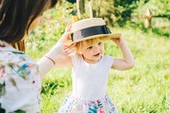 Kleines Mädchen nimmt Mutter ` s Hut Stockfoto
