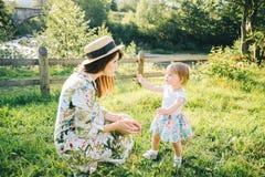 Kleines Mädchen nimmt Mutter ` s Hut Stockbild