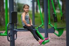 Kleines Mädchen nimmt an Sportausrüstung der im Freienteil liebhaberei stockbild