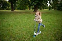 Kleines Mädchen reitet den Roller im Park Lizenzfreie Stockbilder