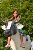 Kleines Mädchen-Reitkuh-Skulptur Stockfotografie