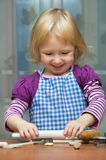 Kleines Mädchen rollt den Teig Stockfoto