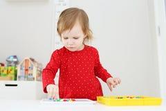 Kleines Mädchen sammelt Mosaik zu Hause Lizenzfreies Stockbild