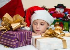 Kleines Mädchen in Sankt-Hut, der die Kästen mit Geschenken nach Chr betrachtet Lizenzfreie Stockfotos