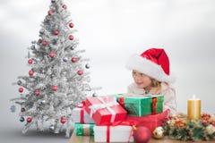 Kleines Mädchen in Sankt-Hut, der mit Stapel Geschenken sitzt Lizenzfreie Stockbilder