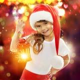 Kleines Mädchen in Sankt-Hut, der rotes Weihnachten hält Stockfoto